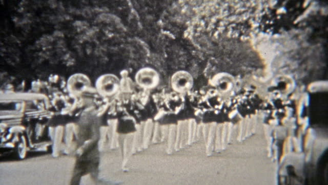 1937: Marching band parading with tuba band horns playing.