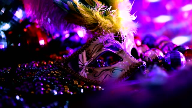 Mardi Gras, Rio carnival mask and colorful decorations. Mardi Gras or Rio Carnival mask and colorful carnival decorations.  Scene includes: gold feathered and sequined mask, colored party lights, and beads.  Objects lie on wooden table. Lockdown.  No people. mardi gras stock videos & royalty-free footage