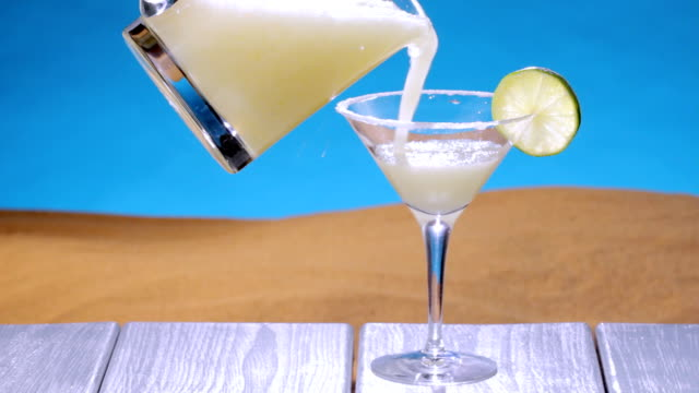 Margarita at the beach A margarita is poured from a pitcher into a glass at the beach margarita stock videos & royalty-free footage