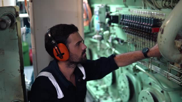 vídeos de stock e filmes b-roll de marine engineer inspecting ship's engine in engine control room - navio
