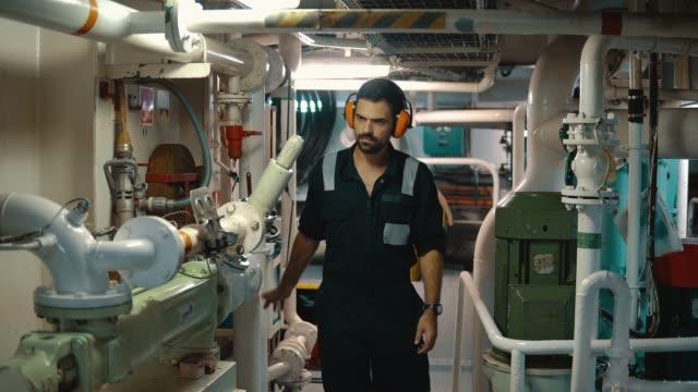 vídeos de stock e filmes b-roll de marine engineer inspecting ship's engine in engine control room - fuzileiro naval