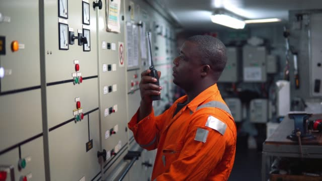 marine engineer officer working in engine room - nigeria video stock e b–roll