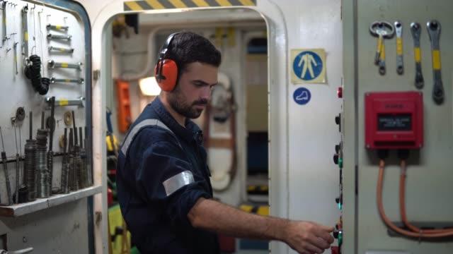 Marine engineer officer working in engine room video