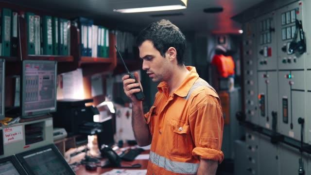Marine Engineer working on radio communication at Engine Control room