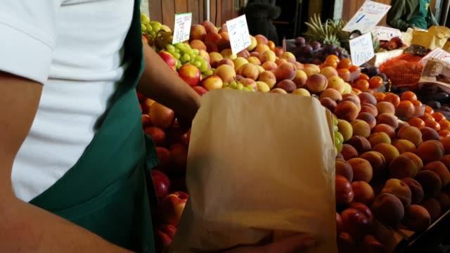 market vendor packing nectarines - video di bancarella video stock e b–roll