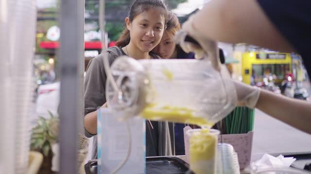 Market vendor pouring fruit smoothie out of blender. Thai street food stall.