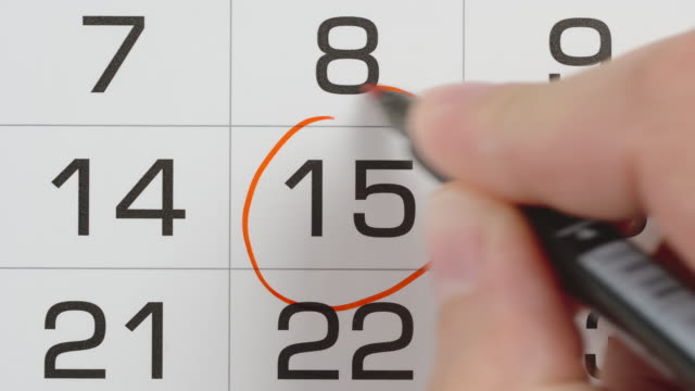 TOP VIEW: Marking a pay day in a paper calendar by red pen - Close Up shot video