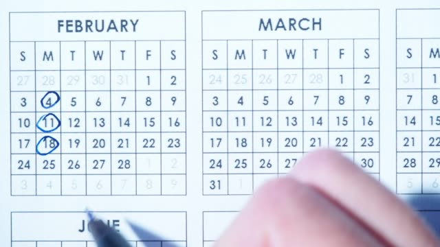 Marking dates in calendar Human hand marking dates in calendar planner. Close-up personal organizer stock videos & royalty-free footage