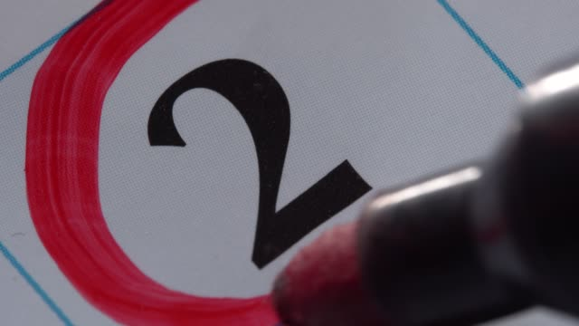 marking the date in the calendar with a red marker - data scritta video stock e b–roll