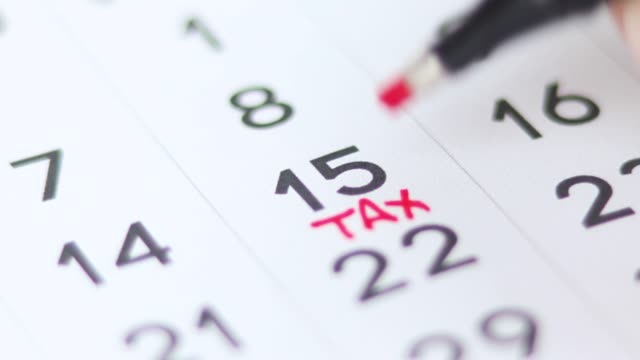 Marking the number 15 and Tax Day on the calendar. 4K Video.