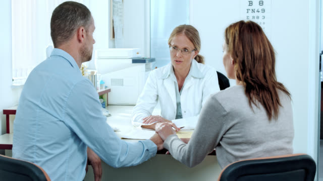 Married couple consulting a female doctor in her office video