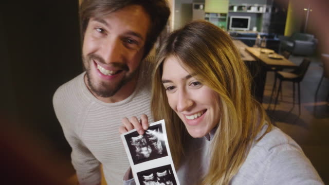 a married couple in love videocall their parents using a tablet, to announce the birth of their son showing the ultrasound. - video call стоковые видео и кадры b-roll