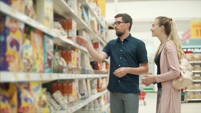 Married couple is shopping in grocery supermarket, choosing cereal for porridge - vídeo