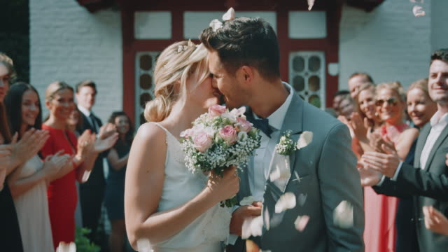 Married couple leaving church while kissing outdoors Happy young newlyweds leaving church and kissing. Smiling guests throwing petals over married couple. They are in wedding ceremony. newlywed stock videos & royalty-free footage