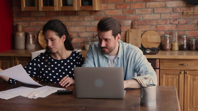 Married couple paying monthly bills using e-bank app on laptop