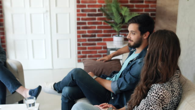 Married couple sits on the sofa in bean bags at a psychologist's reception. People tells about their family problems. The psychologist writes notes in notebook and listens the couple story. video
