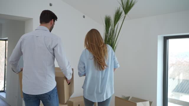 夫婦は新しい家で箱を開梱し、インテリアの配置を計画します ビデオ