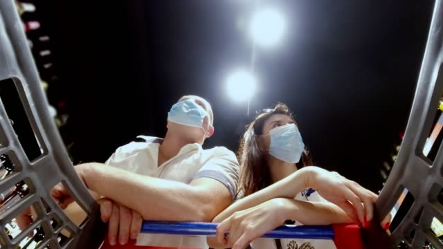 married couple, wearing disposable medical masks and shopping in supermarket during covid-19 outbreak. Protection and prevent measures while epidemic time - vídeo