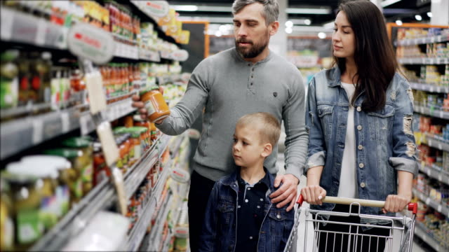 Married couple with cute little son are shopping for food, they are taking glass can from shelf and checking ingredients and expiry date and talking.