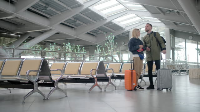 Married couple with suitcases are inside waiting hall of station in daytime - vídeo
