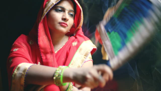 Married Hindu woman uses a hand fan in summer at home.