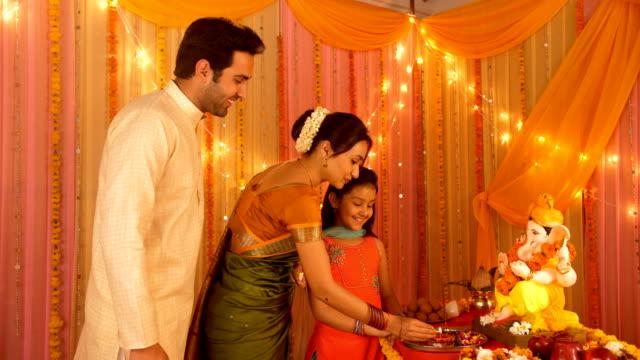 A married woman burning diya for worshiping Lord Ganesha - Husband, Wife, and Daughter