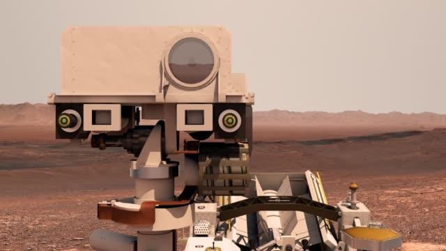 vídeos de stock, filmes e b-roll de marte. o rover perseverança implanta seus equipamentos no pano de fundo de uma verdadeira paisagem marciana. explorando a missão a marte. colônia em marte. elementos deste vídeo fornecidos pela nasa. renderização 3d. - persistência