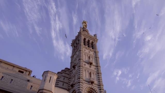 stockvideo's en b-roll-footage met marseille, basilica notre-dame de la garde met toeristen bij zonsondergang - marseille