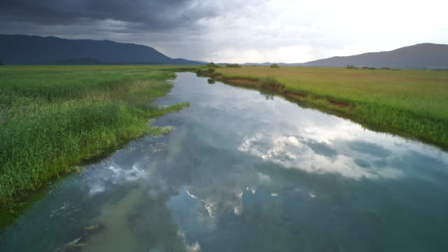 aerial marsh river reflecting grey stormy clouds on its peaceful surface - река стоковые видео и кадры b-roll