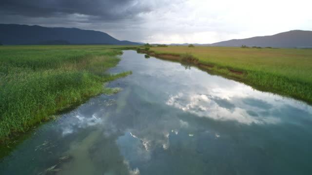 vidéos et rushes de aerial rivière marais réfléchissant gris nuages orageux sur sa surface paisible - eau vive