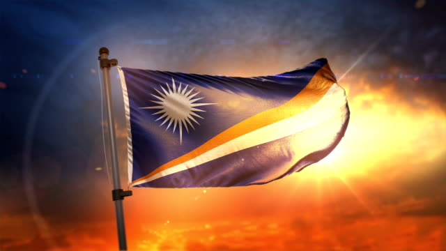 marshall islands flag backlit at beautiful sunrise loop slow motion 4k - majuro video stock e b–roll