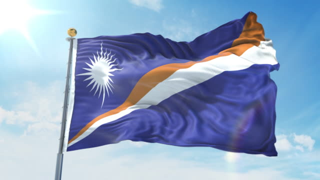 marshall islands flag waving in the wind against deep blue sky. national theme, international concept. 3d render seamless loop 4k - majuro video stock e b–roll