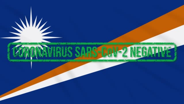 marshall islands swaying flag with green stamp of freedom from coronavirus, loop - majuro video stock e b–roll