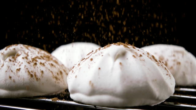 Marshmallow sprinkled with cocoa powder. Slow motion White marshmallows, on a stand, sprinkle cocoa powder, on a black background. Slow motion marshmallow stock videos & royalty-free footage