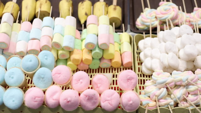 Marshmallows and thai desserts are in the tray. video