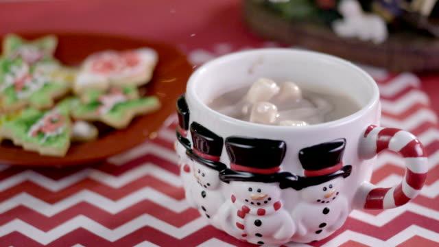 vídeos y material grabado en eventos de stock de malvaviscos caer en una taza de chocolate caliente en cámara lenta - galleta dulces