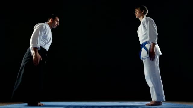 vídeos y material grabado en eventos de stock de maestro de artes marciales usar hakamas tradicional samurai y su arco de joven estudiante uno al otro y tomar postura de batalla. disparo aislado sobre fondo negro y en cámara lenta. - artes marciales