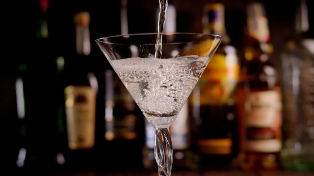 martini hälls i ett glas i baren mot en bakgrund av suddiga flaskor - martini bildbanksvideor och videomaterial från bakom kulisserna