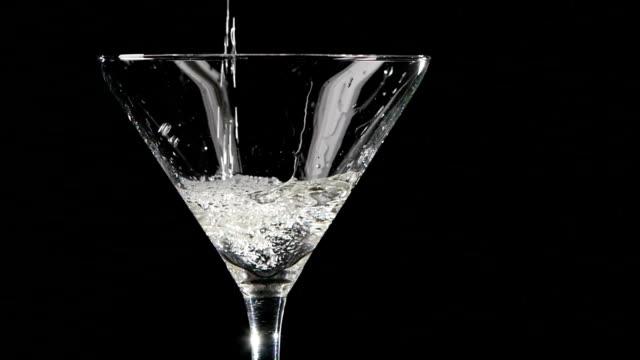 martini viene versato in un bicchiere su sfondo nero.  lento - martini video stock e b–roll