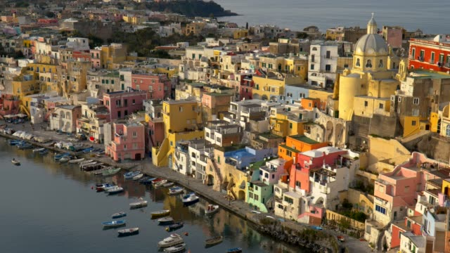 marvelous sunset view of island of procida. naples, italy. colourful italian houses in corriccella village in procida island. panning shot, uhd - procida video stock e b–roll