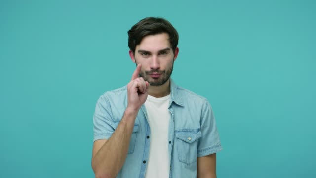 Masculine handsome bossy bearded guy pointing finger at you, looking at camera with serious displeased expression Masculine handsome bossy bearded guy in jeans shirt pointing finger at you, looking at camera with serious displeased expression, confidently making choice. studio shot isolated on blue background desire stock videos & royalty-free footage