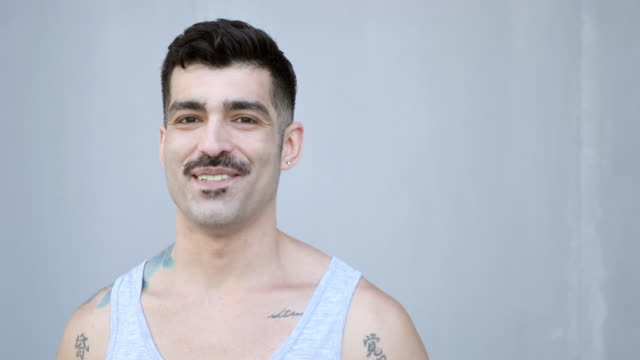masculine latino man with tattoos and mustache - baffo peluria del viso video stock e b–roll