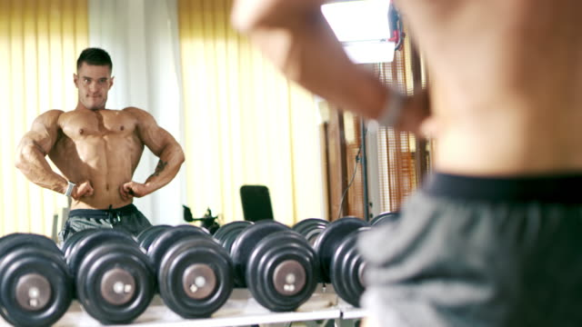 SLO MO Masculine man showing off his muscles Slow motion shot of a young masculine man showing off his muscles in front of the mirror in the gym. Shoot in 8K resolution. macho stock videos & royalty-free footage