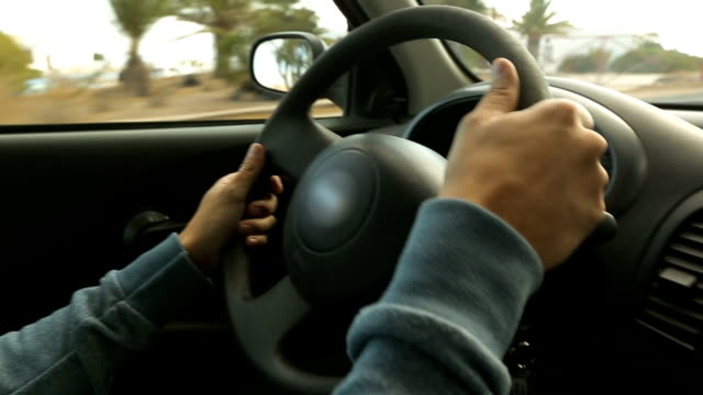 Masculine man's hands firmly holding steering wheel of car riding around city video