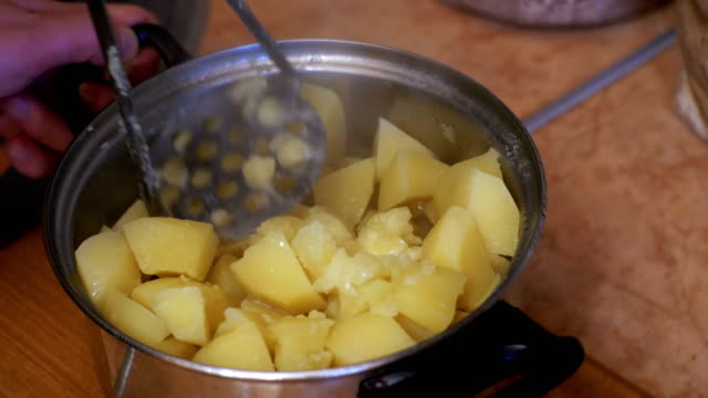 Mashing Potatoes in a Pan on the Home Kitchen Mashing Potatoes in a Pan on the Home Kitchen. Woman chef preparing a potato in the Domestic Kitchen. Cooking food at home. Home atmosphere in the kitchen. prepared potato stock videos & royalty-free footage
