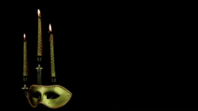 Mask and candles rotate on a black background video
