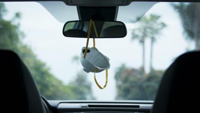 stockvideo's en b-roll-footage met n95 masker dat in de achteruitkijkspiegel van een auto hangt terwijl het drijven - mirror mask