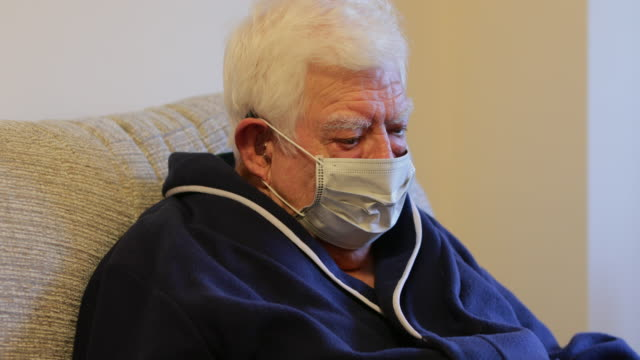 Mask The Virus Senior Caucasian male wearing a medical face mask, sat at home, using his digital tablet. Camera tilts down and back up. persons with disabilities stock videos & royalty-free footage