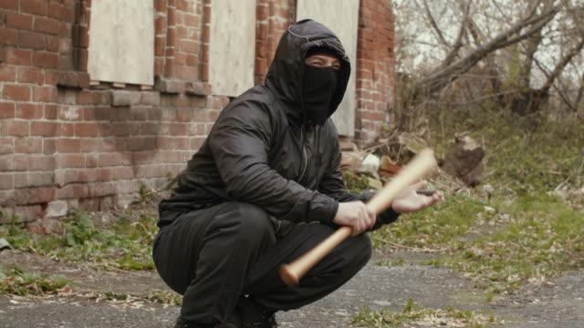 vídeos de stock e filmes b-roll de masked bandit with baseball bat at abandoned place. - going inside eye