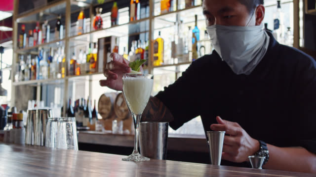Masked Bartender Garnishing Drink at Socially Distanced Bar video